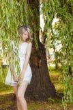 Портрет красивой сексуальной девушки с большими полными губами, с белыми волосами в белом платье около дерева Стоковое Изображение
