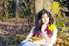 Портрет красивой склонности женщины на дереве с книгой в парке осени Стоковое фото RF