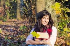 Портрет красивой склонности женщины на дереве с книгой в парке осени Стоковые Фото