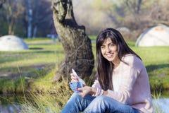 Портрет красивой смеясь над женщины подсчитывая ее деньги в парке Стоковые Фотографии RF