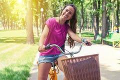 Портрет красивой темн-с волосами женщины на велосипеде в парке Стоковые Изображения