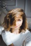 Портрет красивой тонкой сексуальной милой девушки на кровати с белым бельем в белом верхнем белокуром бодрствовании поднимающем в Стоковые Фото