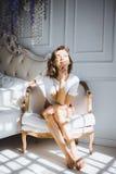 Портрет красивой тонкой сексуальной милой девушки на кровати с белым бельем в белом верхнем белокуром бодрствовании поднимающем в Стоковое Фото