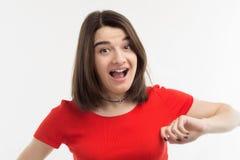 Портрет красивой удивленной молодой женщины нося красную футболку второпях, белая предпосылка, всход студии Стоковое Изображение