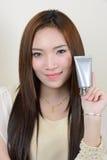 Портрет красивой усмехаясь азиатской женщины держит косметику c стоковые изображения rf