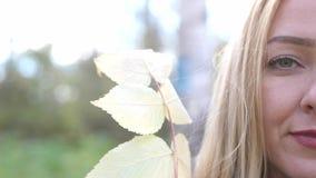 Портрет красивой усмехаясь белокурой девушки с лист осени в лесе в цветах падения замедленное движение 4k 3840x2160 видеоматериал
