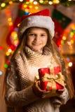 Портрет красивой усмехаясь девушки держа подарочную коробку на рождестве Стоковые Фотографии RF