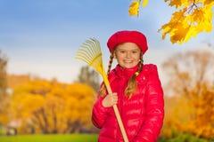 Портрет красивой усмехаясь девушки с грабл Стоковое Изображение
