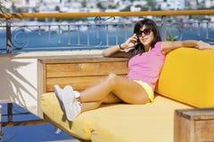 Портрет красивой усмехаясь женщины говоря на телефоне сидя на предпосылке моря Стоковая Фотография