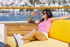 Портрет красивой усмехаясь женщины говоря на телефоне сидя на предпосылке моря Стоковое Фото