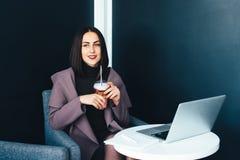 Портрет красивой усмехаясь женщины сидя в кафе с компьтер-книжкой Стоковые Изображения RF