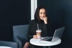 Портрет красивой усмехаясь женщины сидя в кафе с компьтер-книжкой Стоковые Изображения