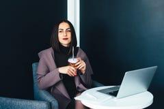 Портрет красивой усмехаясь женщины сидя в кафе с компьтер-книжкой Стоковые Фотографии RF