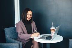 Портрет красивой усмехаясь женщины сидя в кафе с компьтер-книжкой Стоковые Фото