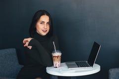 Портрет красивой усмехаясь женщины сидя в кафе с компьтер-книжкой Стоковая Фотография