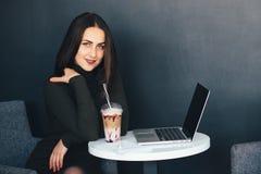 Портрет красивой усмехаясь женщины сидя в кафе с компьтер-книжкой Стоковое Изображение