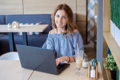 Портрет красивой усмехаясь женщины сидя в кафе с черной компьтер-книжкой Стоковое Изображение RF