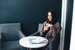 Портрет красивой усмехаясь женщины сидя в кафе Стоковая Фотография RF