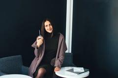 Портрет красивой усмехаясь женщины сидя в кафе Стоковые Фотографии RF