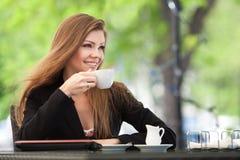 Портрет красивой усмехаясь женщины сидя в кафе с компьтер-книжкой внешней Стоковая Фотография RF