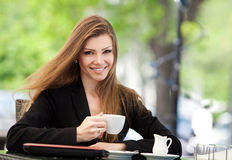Портрет красивой усмехаясь женщины сидя в кафе с компьтер-книжкой внешней Стоковые Фото