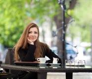 Портрет красивой усмехаясь женщины сидя в кафе с компьтер-книжкой внешней Стоковые Фотографии RF