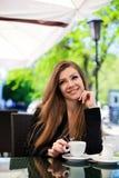 Портрет красивой усмехаясь женщины сидя в кафе с компьтер-книжкой внешней Стоковые Изображения RF