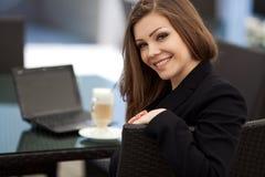 Портрет красивой усмехаясь женщины сидя в кафе с компьтер-книжкой внешней Стоковое фото RF