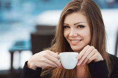 Портрет красивой усмехаясь женщины сидя в кафе с компьтер-книжкой внешней Стоковое Изображение