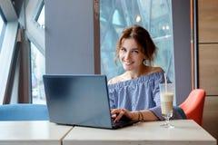 Портрет красивой усмехаясь женщины сидя в кафе с черной компьтер-книжкой Стоковые Фотографии RF