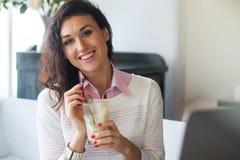 Портрет красивой усмехаясь женщины сидя в кафе Стоковая Фотография