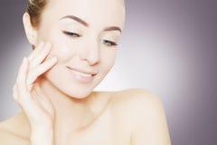 Портрет красивой усмехаясь женщины с совершенной кожей над серым цветом стоковое изображение rf