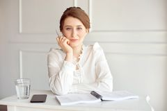 Портрет красивой усмехаясь молодой коммерсантки брюнета в белой рубашке сидя на ярком современном рабочем месте стоковая фотография