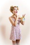 Портрет красивой удивленной молодой женщины смотря камеру & показывая будильник выражая изумление & смотря камеру Стоковые Изображения RF