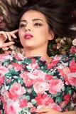 Портрет красивой чувственной женщины лежа вниз на цветках Стоковые Фотографии RF