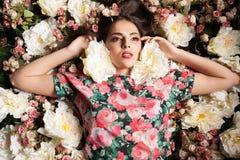 Портрет красивой чувственной женщины лежа вниз на цветках Стоковые Изображения RF