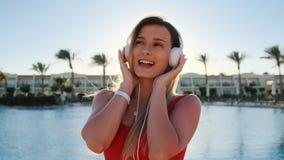 Портрет красивой smilling женщины в красном купальнике и музыки наушников, танцевать и слушать на смартфоне используя приложение сток-видео