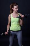 Портрет красивой sporty женщины с гантелями над серым цветом Стоковые Изображения