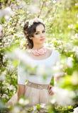 Портрет красивый представлять девушки внешний с цветками вишневых деревьев в цветении во время яркого весеннего дня Стоковые Фото