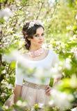 Портрет красивый представлять девушки внешний с цветками вишневых деревьев в цветении во время яркого весеннего дня Стоковые Фотографии RF