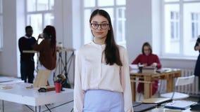 Портрет красивых детенышей сфокусировал кавказскую бизнес-леди в eyeglasses, официальных одеждах смотря камеру на офисе акции видеоматериалы