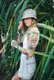 Портрет красивых детенышей татуировал усмехаясь женщину стоя в зеленом густолиственном кусте Стоковые Изображения RF