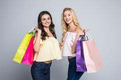 Портрет 2 красивых молодых женщин с хозяйственными сумками на белой предпосылке Стоковые Изображения