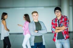 Портрет красивых молодых человеков с пересеченными руками при другие женщины обсуждая в предпосылке Стоковые Фото
