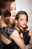 Портрет красивых молодых женщин близнецов в шикарных платьях вечера Стоковые Фотографии RF