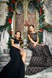 Портрет красивых молодых женщин близнецов в шикарных платьях вечера над предпосылкой рождества Стоковое Изображение