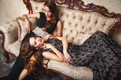 Портрет красивых молодых женщин близнецов в шикарных платьях вечера Стоковое Фото