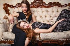 Портрет красивых молодых женщин близнецов в шикарных платьях вечера Стоковые Фото