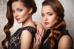 Портрет красивых молодых женщин близнецов в шикарных платьях вечера Стоковая Фотография RF