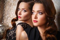 Портрет красивых молодых женщин близнецов в шикарных платьях вечера Стоковое Изображение